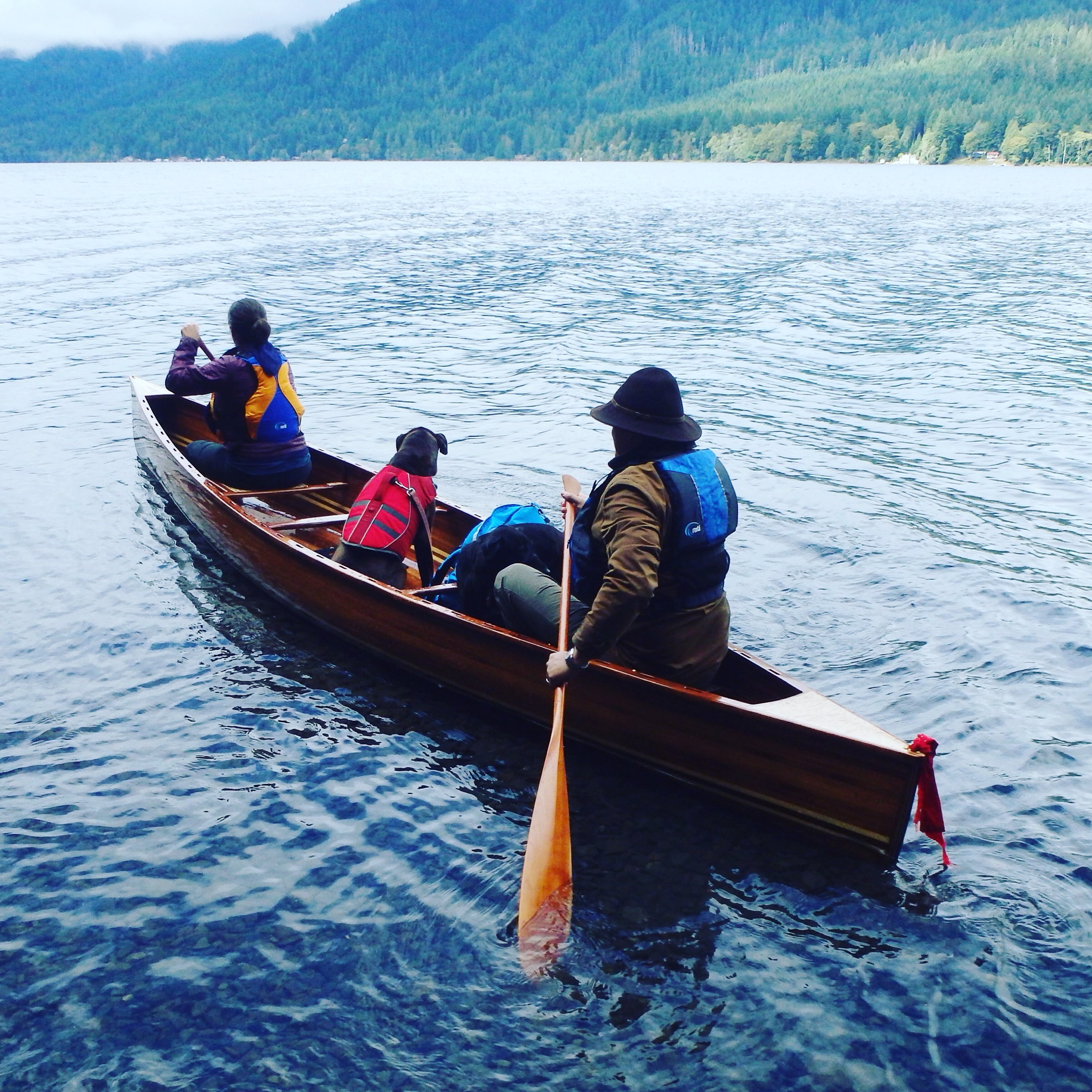 Two people and dogs in a canoe on Lake Crescent, Washington.