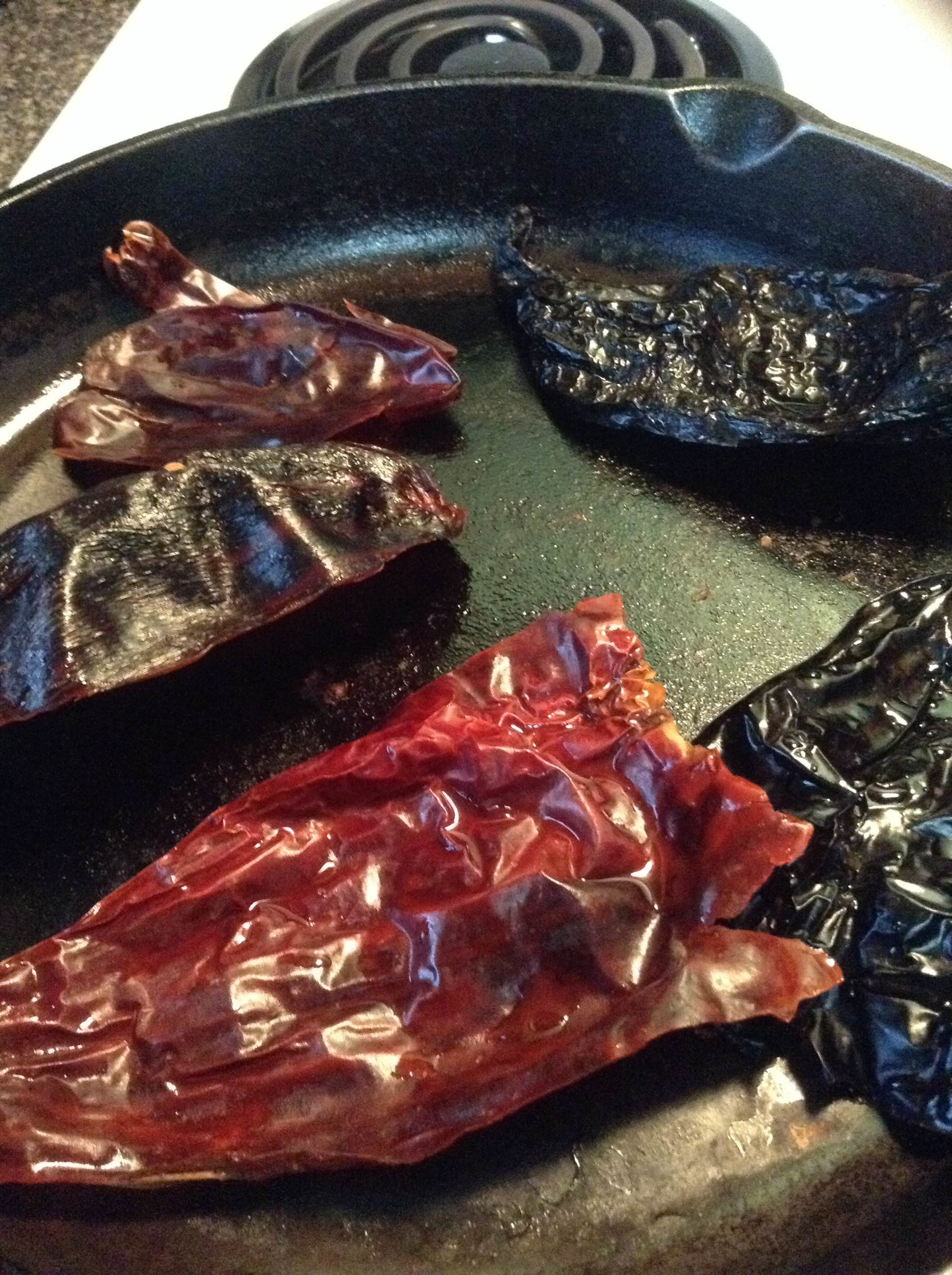 Dried chiles roasting on a cast-iron skillet